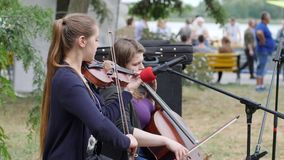 Girls play on musical instruments outdoors, street musicians earn money, artists perform musical composition stock footage