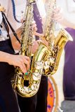 Girls play saxophones on clear sunny day on street. Festive co stock image