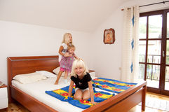 Girls playing. Three sisters are having fun jumping on their parent's bed Royalty Free Stock Images