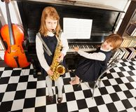 Girls playing on the alto saxophone and piano Royalty Free Stock Images