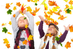 Girls playing with autmn leaves on white Stock Photography