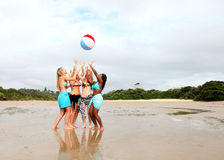 Girls playing with beach ball. Four girls of different races (multi-racial) are playing with a beach ball in the water of a beach in South Africa Royalty Free Stock Photography
