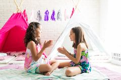 Girls Playing Clapping Game While Enjoying Pajama Party. Side view of cute girls playing clapping game while enjoying pajama party at home royalty free stock photography