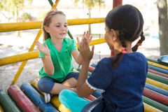 Girls playing clapping game while sitting on jungle gym Stock Image