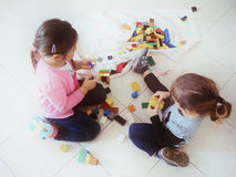 Girls playing with colored bricks Stock Photo