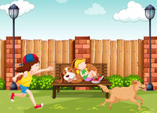 Girls playing with dogs in park Royalty Free Stock Image