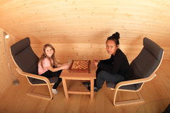 Girls playing draughts Stock Images