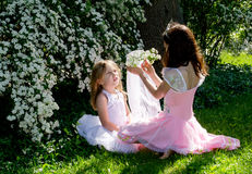 Girls playing dressup in the sunlight. Two young girls play dressup in the garden sunlight Stock Photography