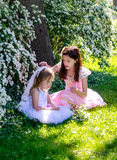 Girls playing dressup in the sunlit garden Royalty Free Stock Image