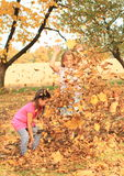 Girls playing with fallen leaves Royalty Free Stock Images