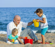 Girls playing with   father near sea. Royalty Free Stock Photo