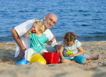 Girls playing  with  father near sea. Stock Image