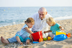 Girls playing with   father near sea. Royalty Free Stock Image