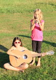 Girls playing flute and guitar Stock Photo