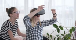 Girls playing game with virtual reality goggles and mobile phone at home stock footage