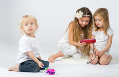 Girls playing on a gaming device and a boy playing Royalty Free Stock Images