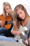 Girls playing guitar Royalty Free Stock Photos