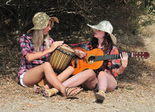 Girls playing Guitar and Djembe Outdoors Stock Image