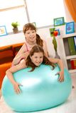 Girls playing with gym ball in living room Stock Photography