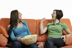 Girls playing hand games on orange sofa Royalty Free Stock Photography