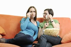 Girls playing hand games on orange sofa Royalty Free Stock Photos