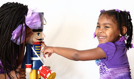 Girls Playing With Holiday Nutcracker. Two pretty sister girls play with a Christmas holiday nutcracker Stock Photo