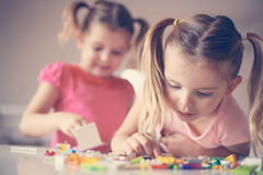 Girls playing at home. Girls playing with Lego blocks at home. Focus on one girl Royalty Free Stock Images