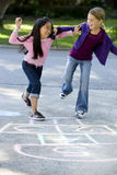 Girls playing hopscotch. Multiracial friends having fun playing hopscotch on driveway Royalty Free Stock Photo