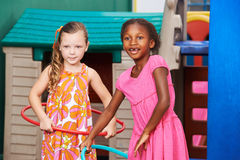 Girls playing with hula hoop in kindergarten Stock Photography