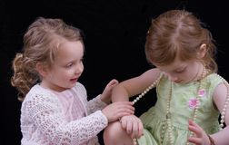 Girls playing with jewelry. Sisters trying on antique jewelry Royalty Free Stock Photo