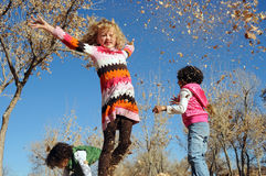 Girls playing in leaves. Young girls playing in leaves on a sunny autumn day Stock Photography