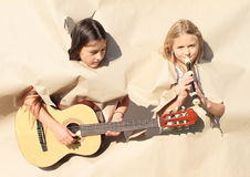 Girls playing music instruments thru holes. Heads and hands of little kids - girls playing guitar and flute thru holes in big paper Royalty Free Stock Image