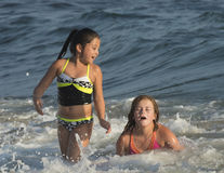 Girls playing in the ocean. An eight year-old Amerasian girl in a black and yellow two piece swimsuit is playing in the ocean with her ten year-old female cousin Royalty Free Stock Photography