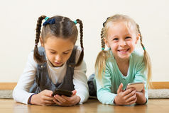 Girls playing online with phones Stock Images