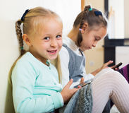 Girls playing online with phones Royalty Free Stock Photos