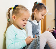 Girls playing online with phones Royalty Free Stock Photography
