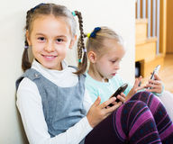 Girls playing online with phones Royalty Free Stock Image