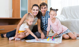 Girls playing with parents at board game on floor Royalty Free Stock Images