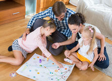 Girls playing with parents at board game on floor Royalty Free Stock Image