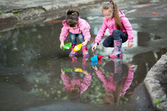 Girls playing in puddle. Little girls, wearing a pink jacket, playing with colorful paper ship, in the puddle Royalty Free Stock Photos