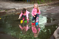 Girls playing in puddle. Little girls, wearing a pink jacket, playing with colorful paper ship, in the puddle Stock Image