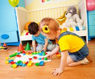 Girls playing with puzzle Royalty Free Stock Image