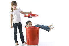 Girls playing with red bin Royalty Free Stock Image