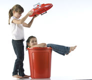 Girls playing with red bin Royalty Free Stock Photography