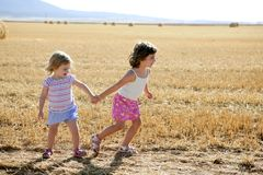 Girls playing with the round wheat dried bales Royalty Free Stock Image