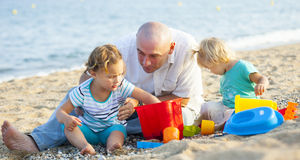 Girls playing with sand next to dad Royalty Free Stock Photography