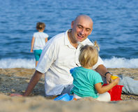 Girls playing with sand next to dad Royalty Free Stock Photo