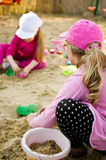 Girls playing in sandbox. Two cute girls playing in sandbox with colorful toys together Royalty Free Stock Photos