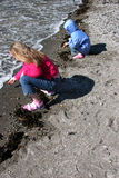 Girls playing on sandy beach. Two girls playing on the beach in the spring Stock Photos