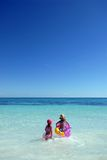 Girls playing in sea. Two little girls having fun in the sea (ocean), clear blue sky and water Stock Image